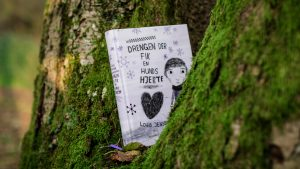 "The Danish book ""Drengen der fik en hunds hjerte"" is placed in a tree with green moss spots"