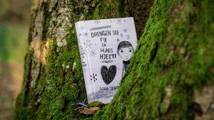 """The Danish book """"Drengen der fik en hunds hjerte"""" is placed in a tree with green moss spots"""