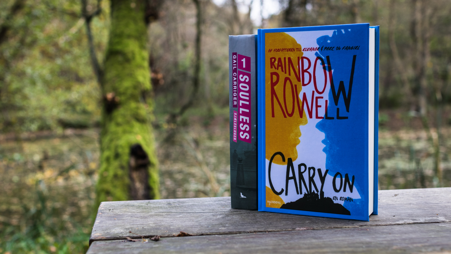 Soulles by Gail Carriger and Carry On by Rainbow Rowell on a bench by a lake