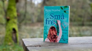 The book Små frø (Small Seeds) by Mette Hegnhøj on a bench in the woods.