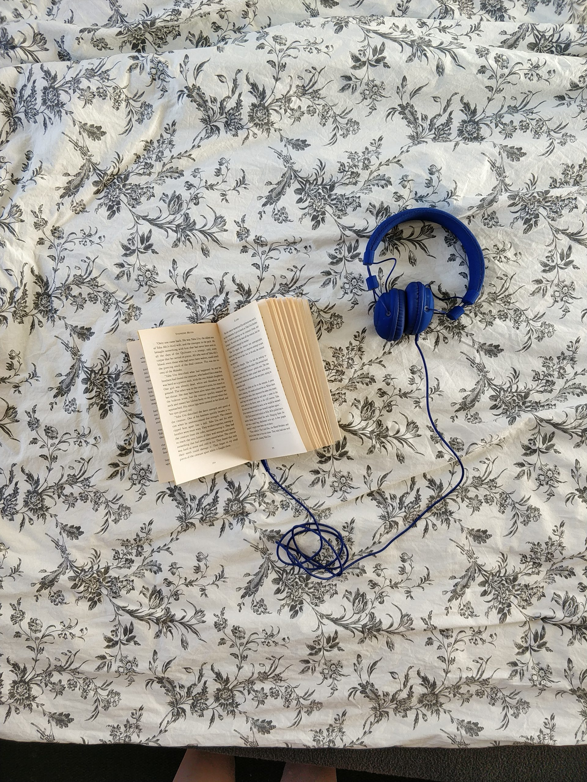 A book on a flowery background with a set of headphones attached to it