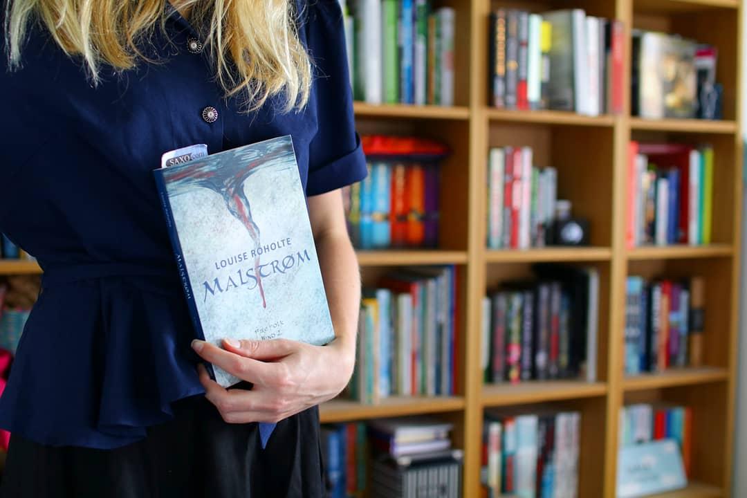 Jeg står foran min bogreol med Malstrøm af Louise Roholte i hånden
