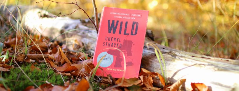 Bogen Wild af Cheryl Strayed står lænet op ad en træstamme i skovbunden. Skovbunden er dækket af brune efterårsblade og baggrunden er lys og gullig.