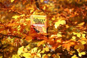 Tredje bog i Hunger Games serien på en gren mellem de gule og orange efterårsfarvede blade fra et træ i skoven.