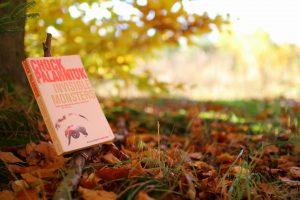 Bogen Invisible Monsters til venstre på billedet. I baggrunden ser man en sløret busk og en lysning i skoven.
