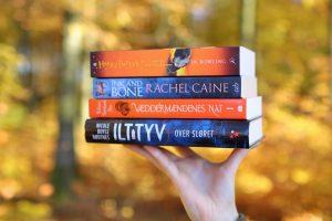 Jeg balancerer en lille stak fantasybøger med en hånd. I baggrunden ses den efterårsklædte skov. Bøgerne er: Ilttyv, Væddermændenes nat, Ink and Bone, Harry Potter and the Half-Blood Prince.