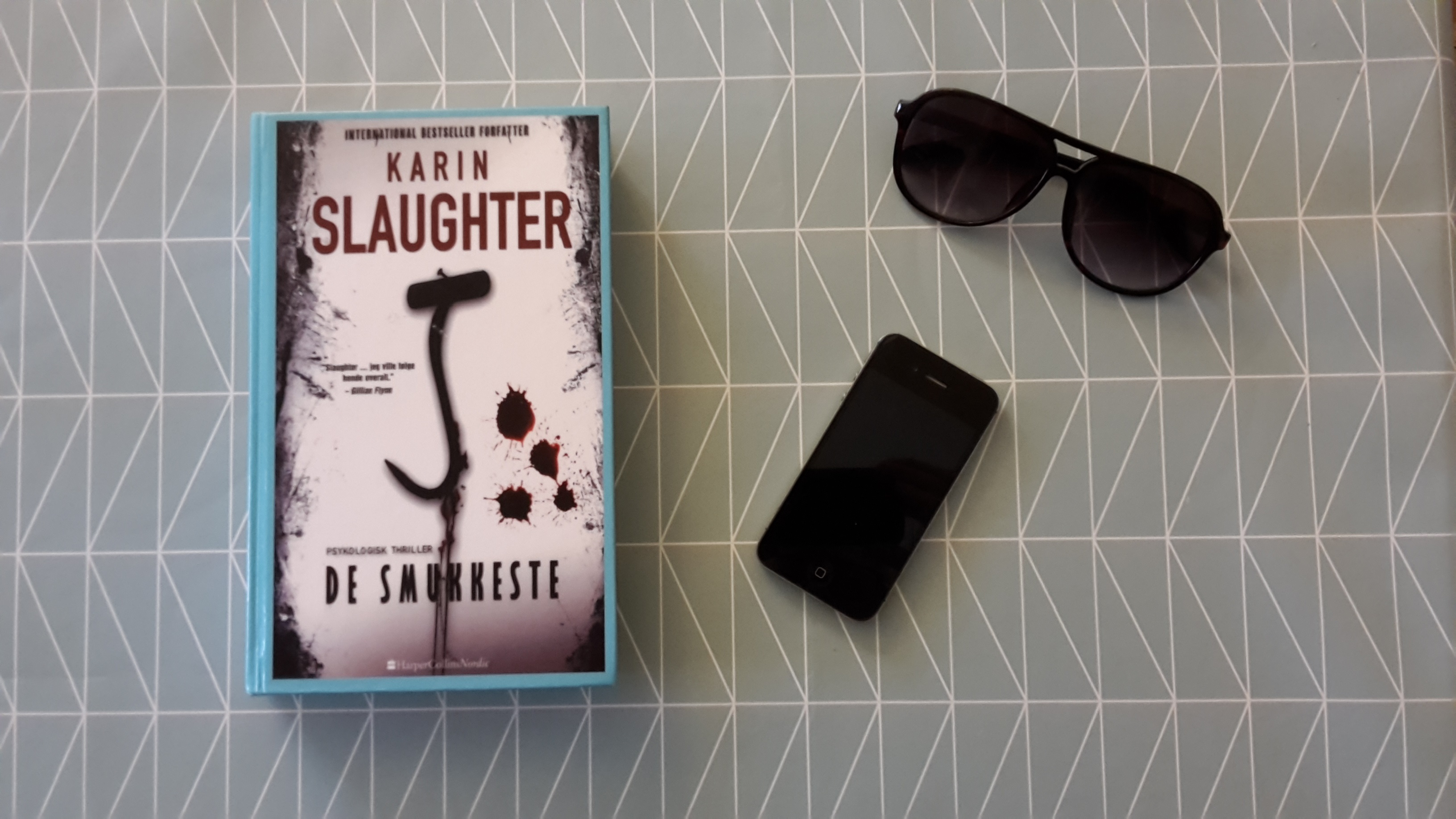The book Pretty Girls by Karin Slaughter lies on a table with a smart phone and a pair of sunglasses. The table is covered in a blue table cloth.