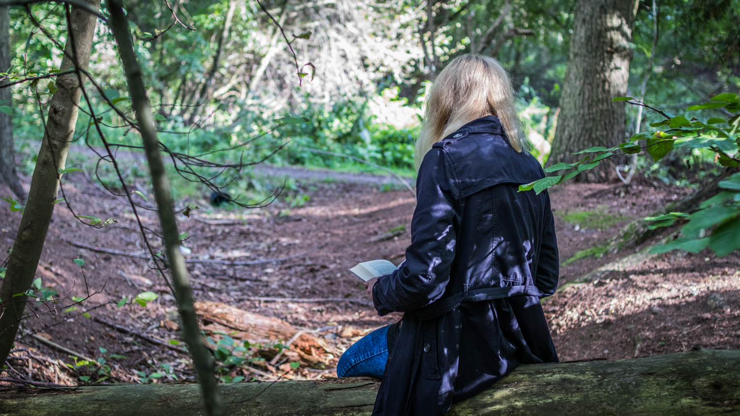 A young woman (me) reading a book in the forest