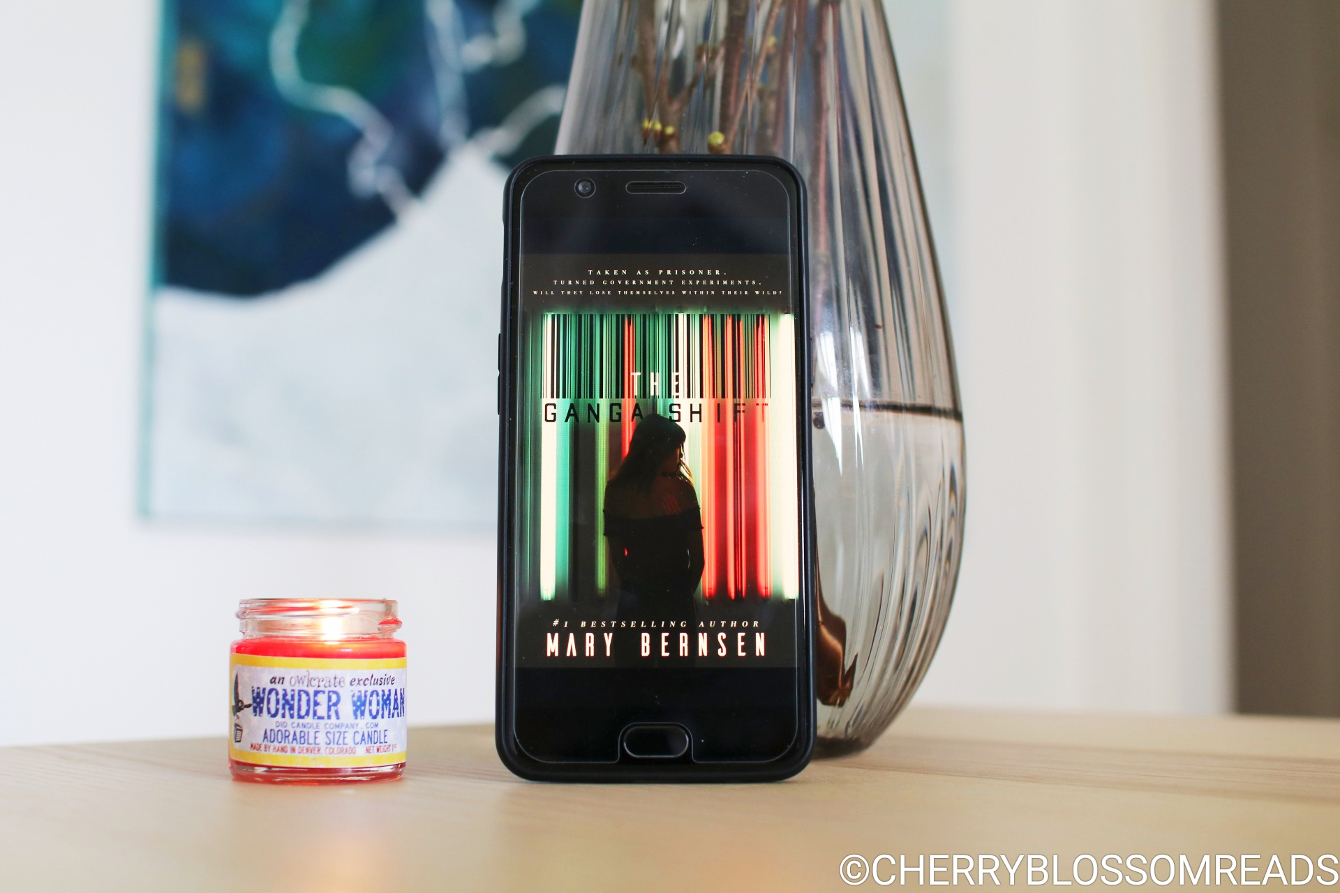 The cover of the e-book The Ganga Shift on a mobile phone next to a grey vase and a read burning candle