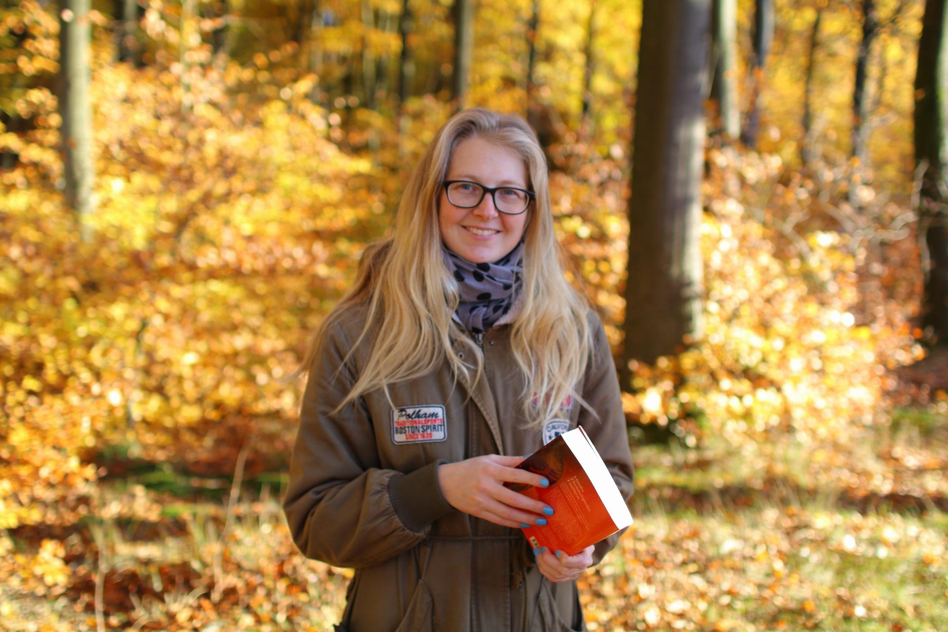Billedet viser mig, der står i skoven med en orange bog i hånden. I baggrunden ser man træer og blade i efterårets gule og orange farver.